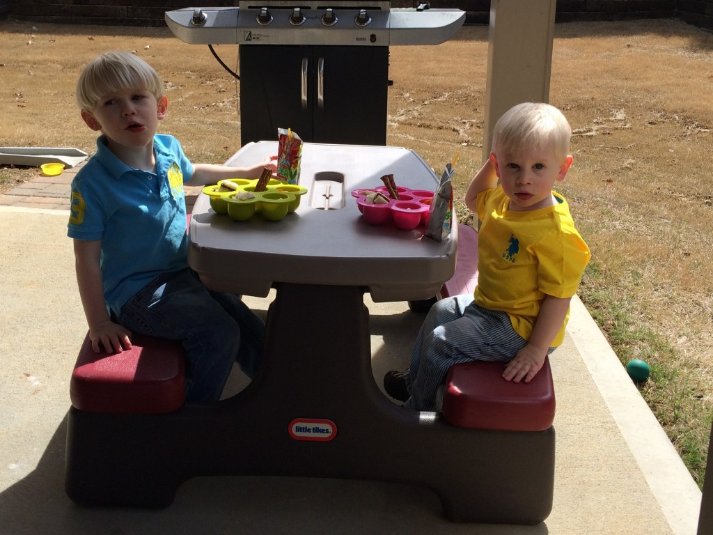 Toddlers eating picnic lunch outside